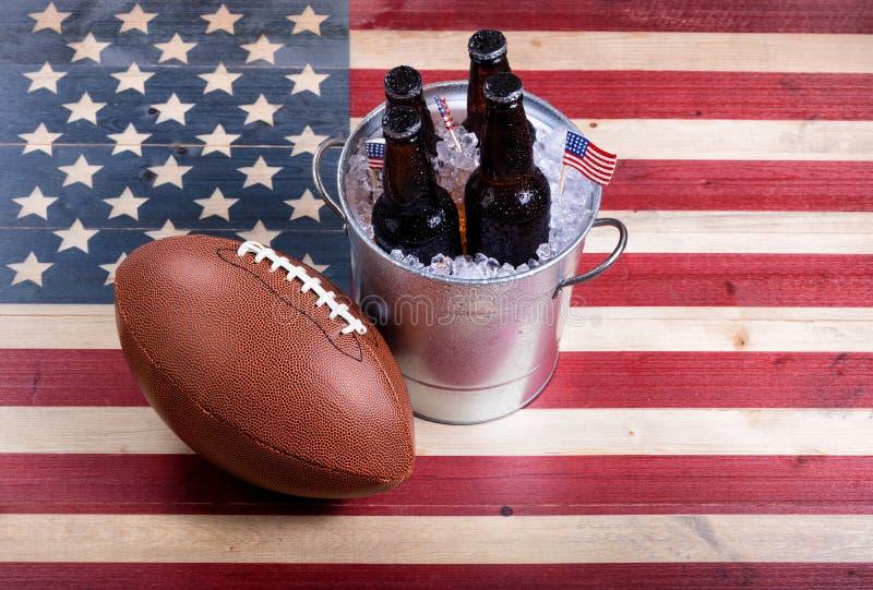 Amerikansk fotboll och iskallt öl på lantliga träUSA sjunker royaltyfria bilder