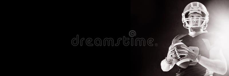 Amerikansk fotbollsspelare i hjälmen som rymmer rugbybollen royaltyfri foto