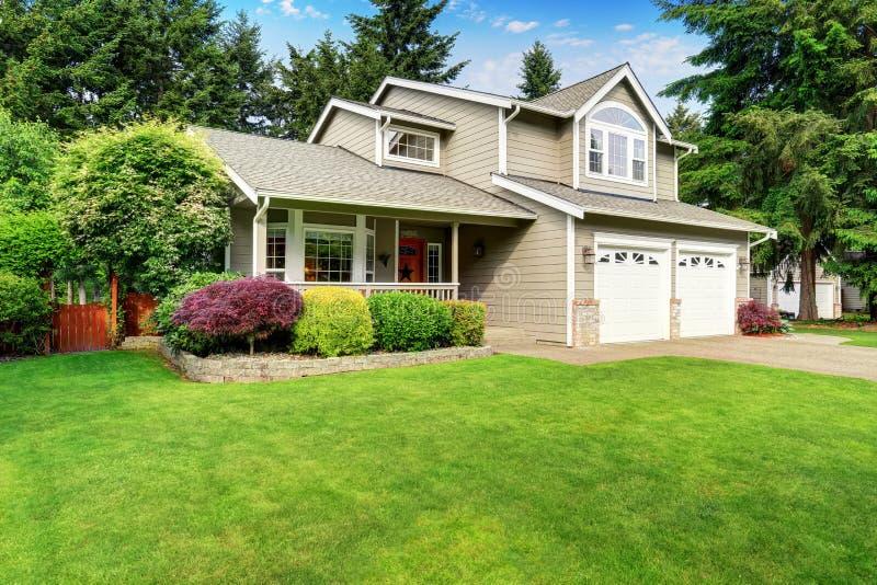 Amerikansk husyttersida med det dubbla garaget och väl hållen gräsmatta arkivfoton