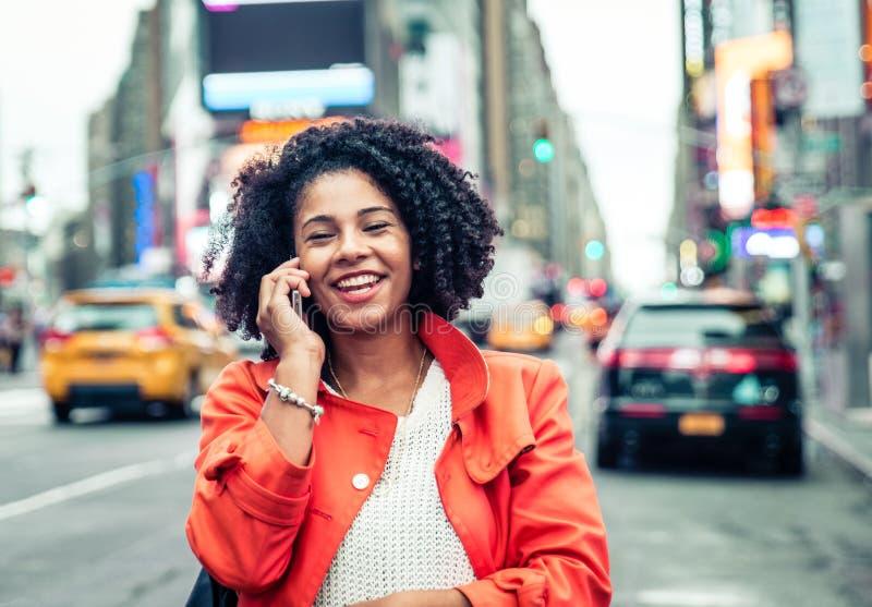 Amerikansk kvinna som gör en påringning i Time Square arkivfoton