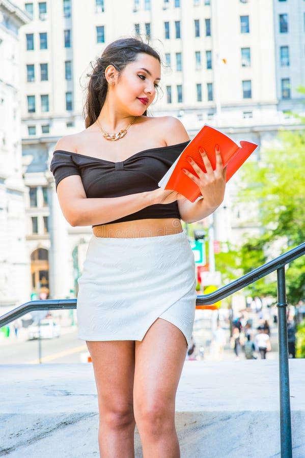 Amerikansk kvinnlig högskolestudentläsebok som studerar på universitetsområde royaltyfri fotografi