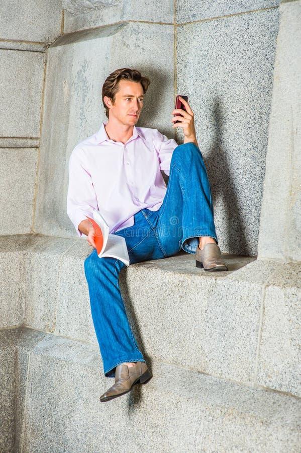 Amerikansk manläsebok som utanför smsar på mobiltelefonen royaltyfri foto