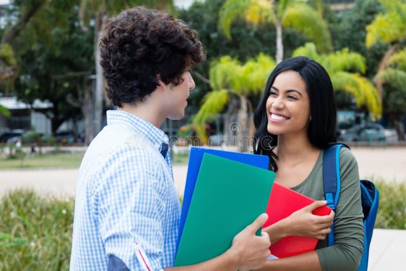 Amerikansk manlig student som talar med den indiska kvinnliga studenten royaltyfri fotografi