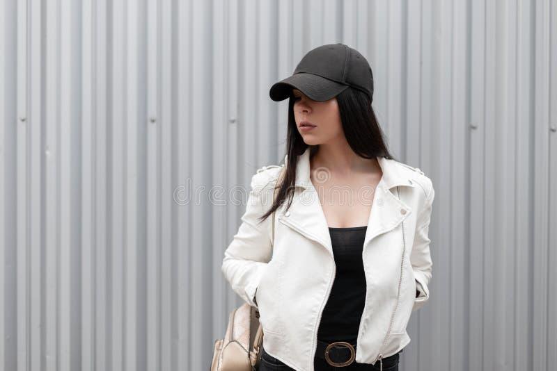 Amerikansk nätt ung brunettkvinna i ett moderiktigt vitläderomslag i en stilfull svart baseballmössa i en T-tröja royaltyfria foton