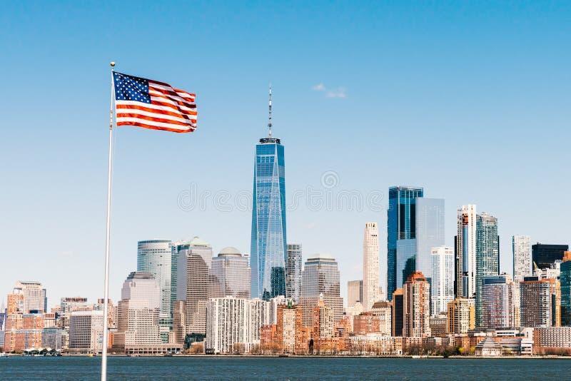 Amerikansk nationsflagga på solig dag med den New York City Manhattan ön i bakgrund Begrepp för Förenta staternanationsymbol royaltyfri foto