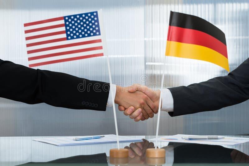 Amerikansk och tysk affärsman som skakar händer royaltyfria bilder