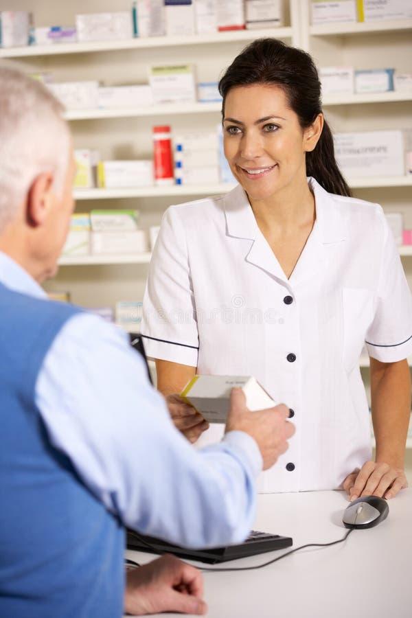 Amerikansk pharmacist som fördelar till den höga mannen arkivfoto