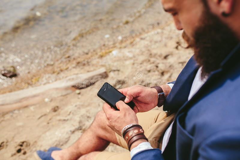 Amerikansk skäggig man som använder telefonen nära floden royaltyfria bilder