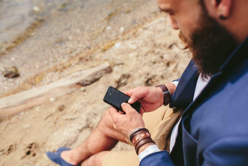 Amerikansk skäggig man som använder telefonen nära floden arkivbild