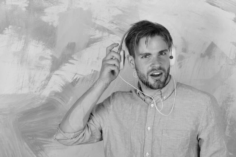 Amerikansk stilig skäggig grabb med hörlurar Gladlynta tonårs- lyssnande sånger för dj via hörlurar Musikalisk livsstil royaltyfri foto