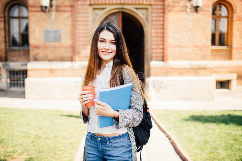 Amerikansk universitetsstudent som ler med kaffe- och bokpåsen på universitetsområde royaltyfria foton