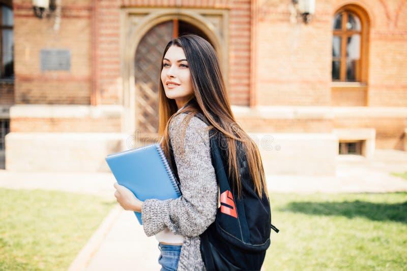 Amerikansk universitetsstudent som ler med kaffe- och bokpåsen på universitetsområde royaltyfria bilder