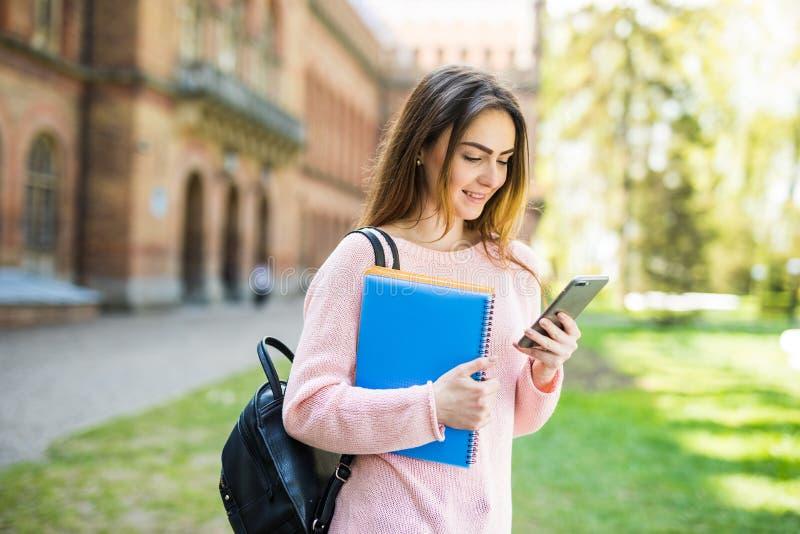 Amerikansk universitetsstudent som ler med kaffe- och bokpåsen på universitetsområde med telefonen i händer arkivfoto