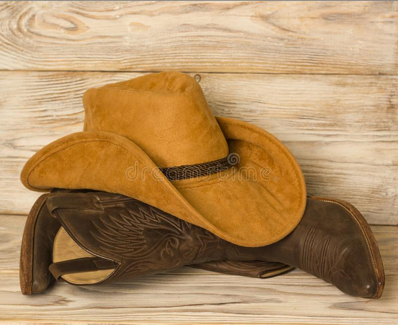 Amerikansk västra cowboykängor och hatt på wood texturbakgrund arkivbild