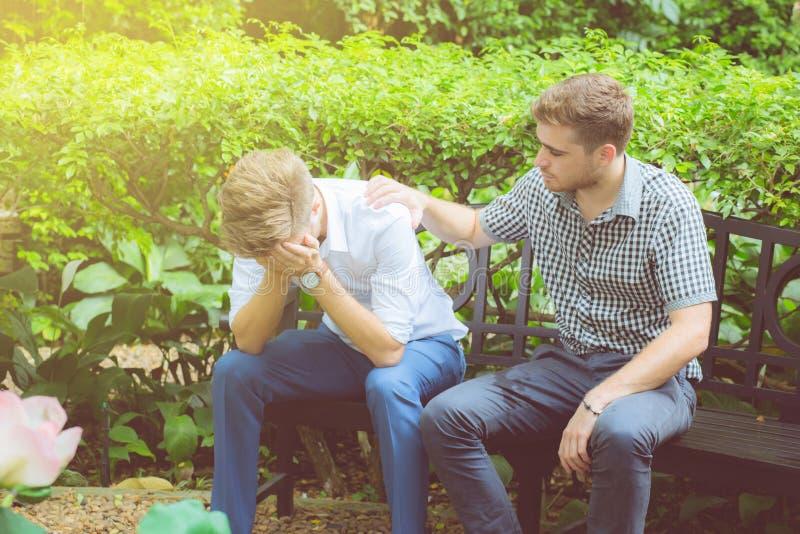 Amerikanska affärsmän som tröstar vännen Frustrerad ung man som tröstas av hans vän i trädgård royaltyfria bilder