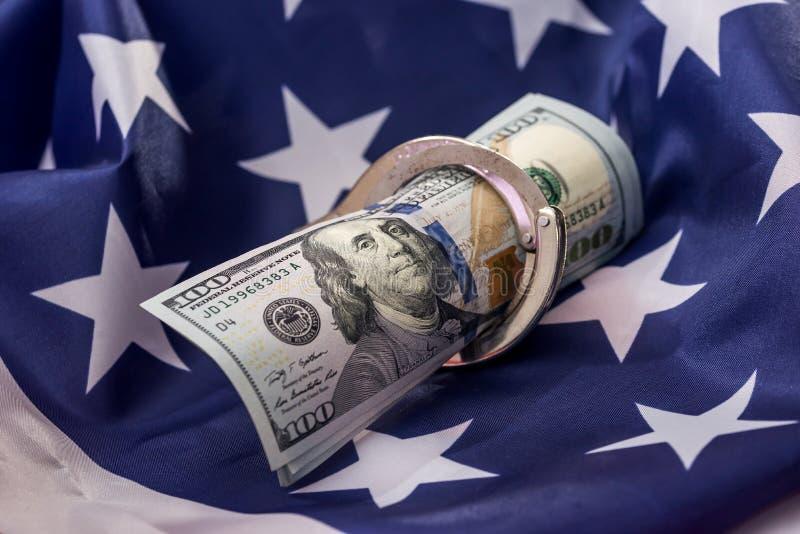 Amerikanska dollar i handbojor på nationsflaggan royaltyfria foton