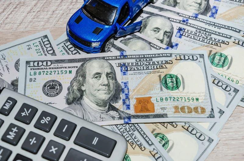 Amerikanska dollar räknemaskin och en blå leksakbil på en trätabell royaltyfria foton