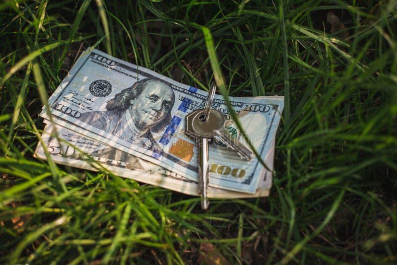 Amerikanska dollarräkning och tangenter på grönt gräs royaltyfri foto