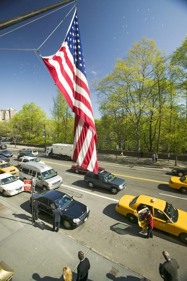 Amerikanska flaggan flyger över Central Park i vår med gula taxi som är främsta av Helmsely, parkerar gränden, Manhattan, New Yor royaltyfria foton