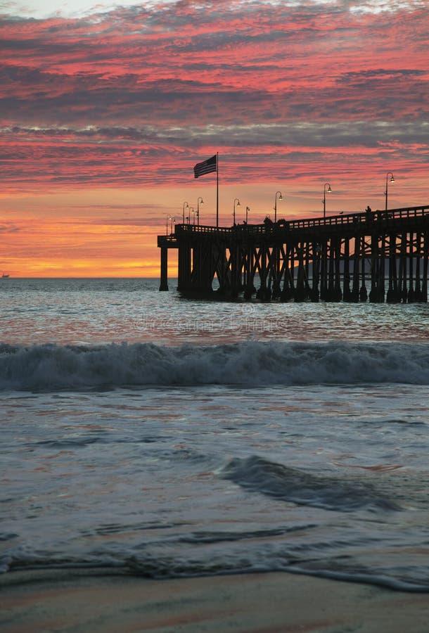 Amerikanska flaggan flyger över Ventura Pier på solnedgången, Ventura, Kalifornien, USA royaltyfri foto