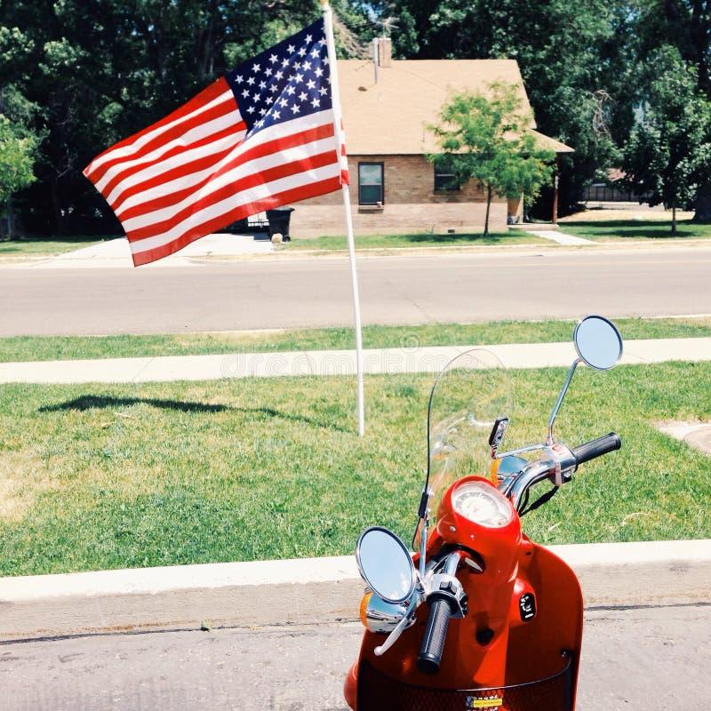 Amerikanska flaggan med en sparkcykel arkivbild