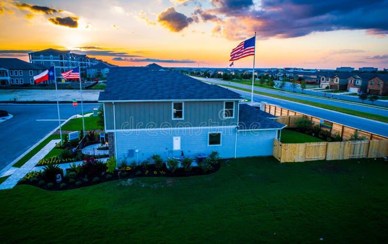 Amerikanska flaggan med förort och Texas Flag för ny utveckling på solnedgången arkivfoton