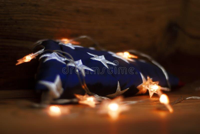 Amerikanska flaggan med girlanden på en träbakgrund för Memorial Day och andra ferier av Amerikas förenta stater royaltyfri fotografi