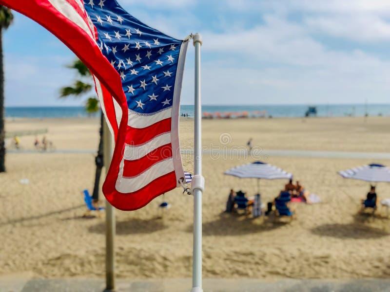 Amerikanska flaggan med stranden på backgrounen fotografering för bildbyråer