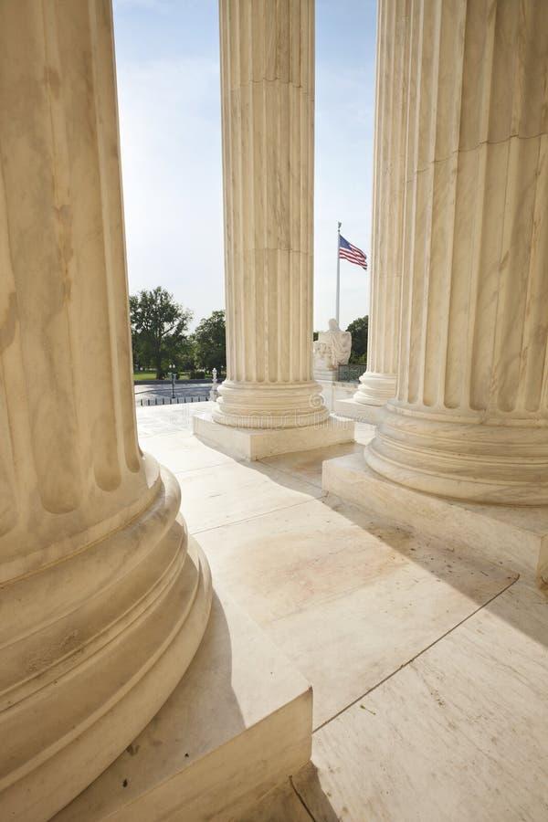 Amerikanska flaggan mellan kolonner av högsta domstolen royaltyfri fotografi