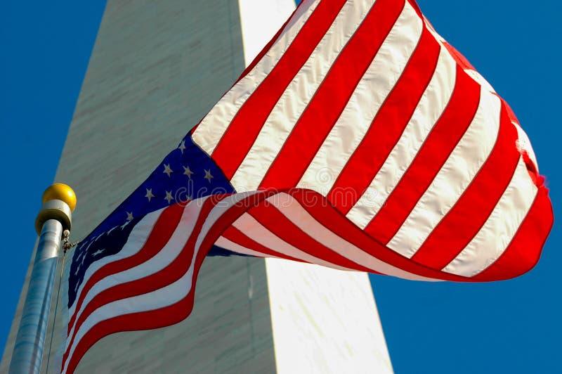 Amerikanska flaggan mot Washington Monument och blå himmel arkivbild