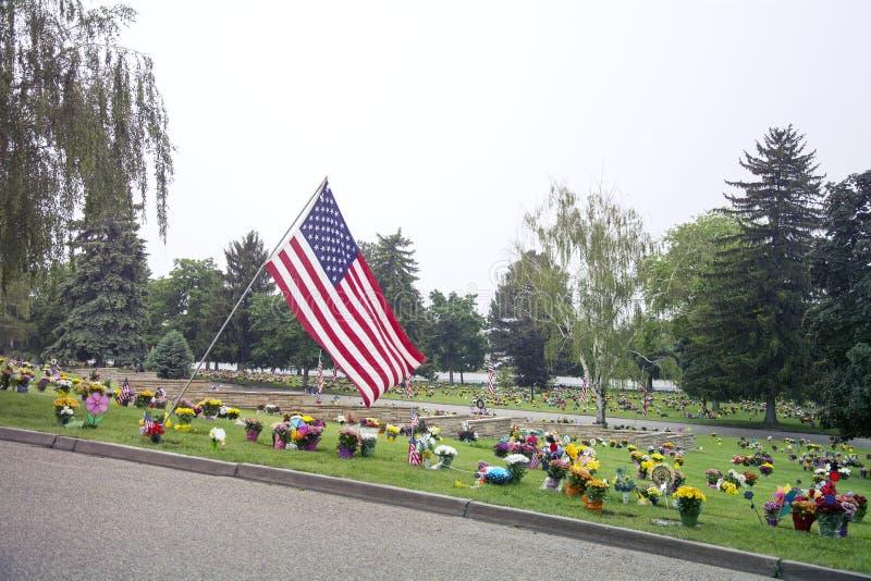 Amerikanska flaggan och blommor på Graveside royaltyfri foto