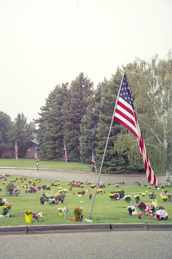 Amerikanska flaggan och blommor på Graveside royaltyfri bild