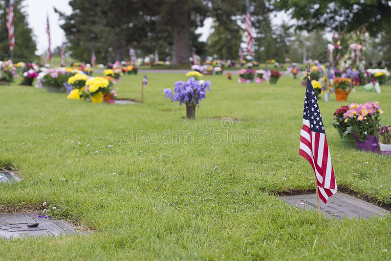 Amerikanska flaggan och blommor på veteranGraveside arkivfoton