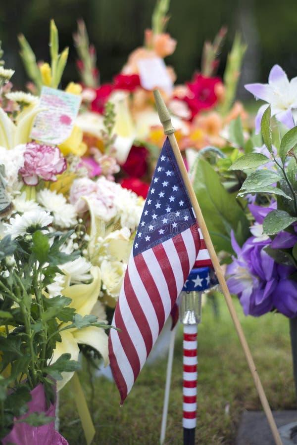 Amerikanska flaggan och blommor på veteranGraveside arkivbilder