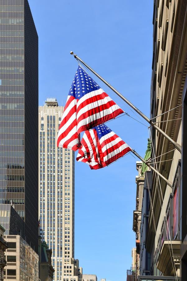 Amerikanska flaggan på bakgrund av berömda skyskrapor i i stadens centrum Manhattan stad New York f?renade tillst?nd arkivfoton