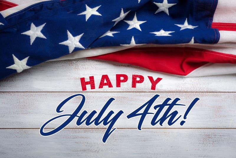 Amerikanska flaggan på en vit sliten träbakgrund med den Juli 4th hälsningen royaltyfria foton