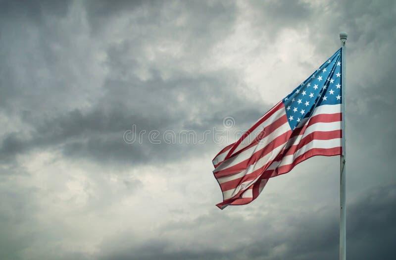 Amerikanska flaggan på ett molnigt mörker royaltyfria bilder