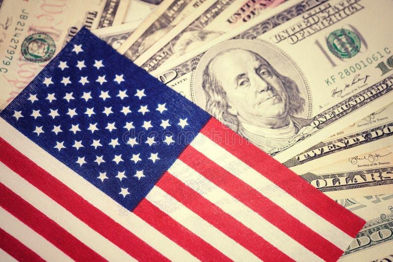 Amerikanska flaggan på hundra bakgrund för dollarräkning Pengar kontant bakgrund finansiellt begrepp Tappning retro blick royaltyfri bild
