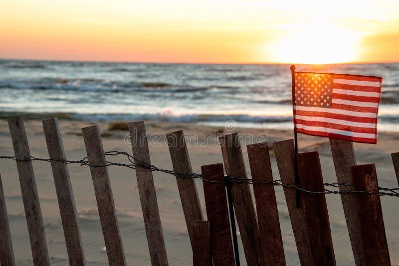Amerikanska flaggan på strandstaketet med solnedgångglöd royaltyfri bild