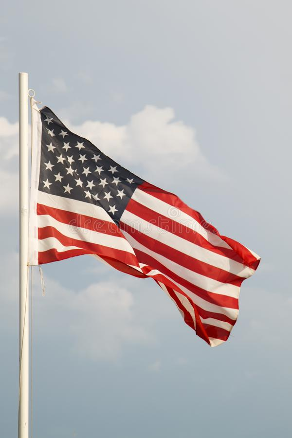 Amerikanska flaggan p? en bl? himmel med molnbakgrund royaltyfri bild