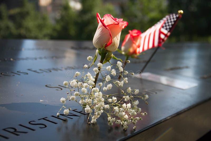 Amerikanska flaggan, ros och blomma på internationell handelmitten för 911 minnesmärke royaltyfria foton