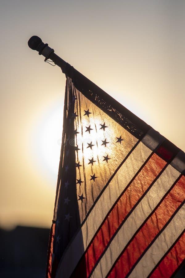 Amerikanska flaggan som ?r bakbelyst p? skymning royaltyfria foton
