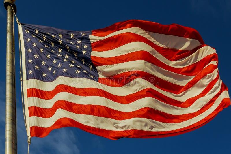 Amerikanska flaggan som blåser i vinden mot en härlig cloudscape royaltyfri fotografi