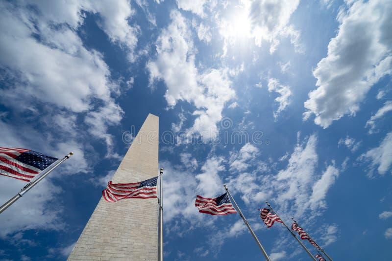 Amerikanska flaggan som bl?ser i vinden med Washington Monument l?ngs National Mall Delvis molnig himmel royaltyfria bilder