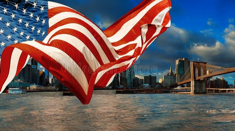 Amerikanska flaggan som flyger New York City manhattan för a-horisontsikt den i stadens centrum horisonten arkivbild