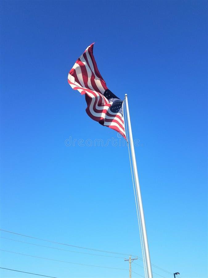 Amerikanska flaggan som framme vinkar i vinden av en bl? himmel arkivbild