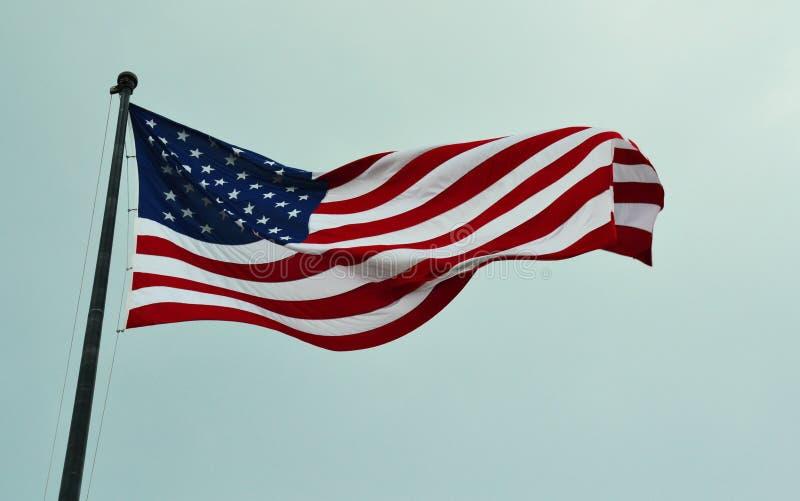 Amerikanska flaggan som vinkar i en himmel arkivfoto