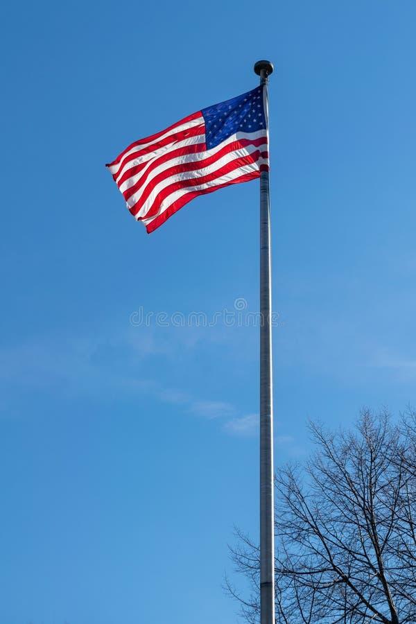Amerikanska flaggan, stj?rnor & band som vinkar i vinden, mot en h?rlig bl? himmel p? en solig sommardag royaltyfri bild