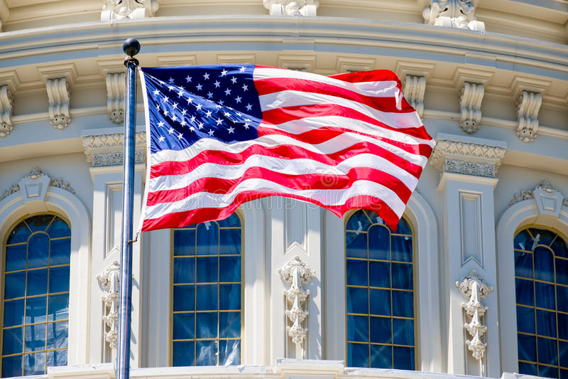 Amerikanska flaggan vinkar i fron av Kapitoliumbyggnaden arkivfoton