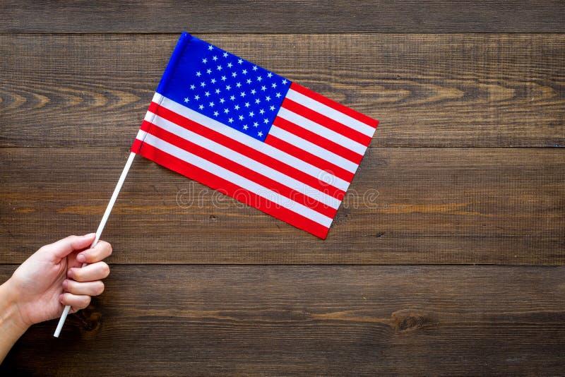 Amerikanska flagganbegrepp Liten flagga för handhåll på mörkt träutrymme för kopia för bästa sikt för bakgrund arkivfoton